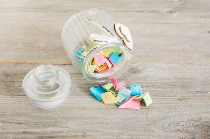 Glass jar with handmade wooden hearts decorations and ribbon filled with colorful pastel paper notes spilling over.